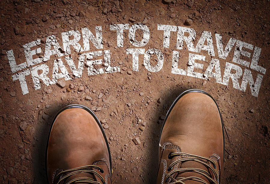 Top View of Boot on the trail with the text Learn to Travel. Travel to Learn.